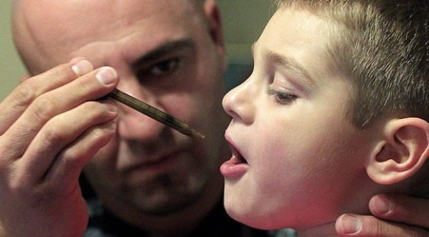 A father administers a dose of cannabis oil to his son